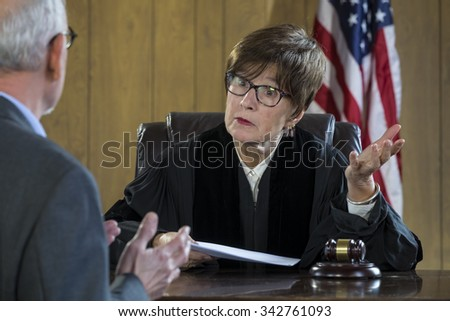 Female judge with male attorney in courtroom - stock photo