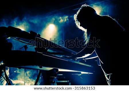Female keyboards player on stage during concert, backlight, colors intentionally altered - stock photo