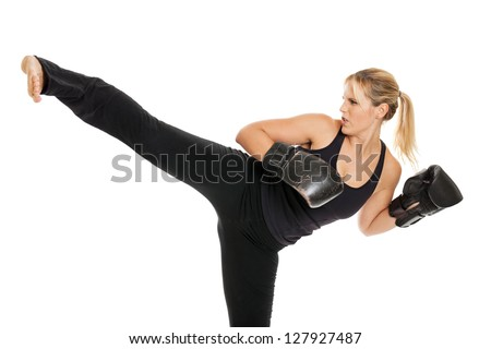 Female kickboxer doing a side kick isolated on a white background - stock photo