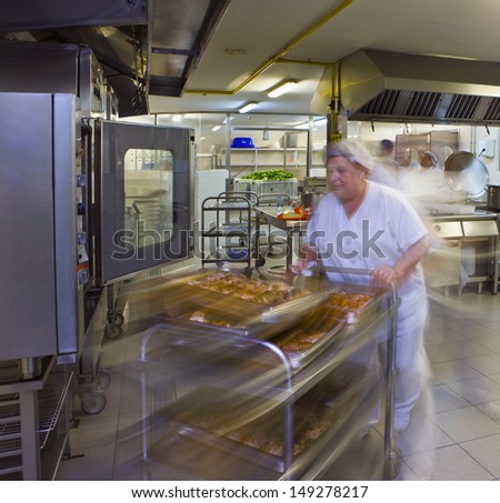 Female kitchen porter pushes a trolley of pastries - stock photo