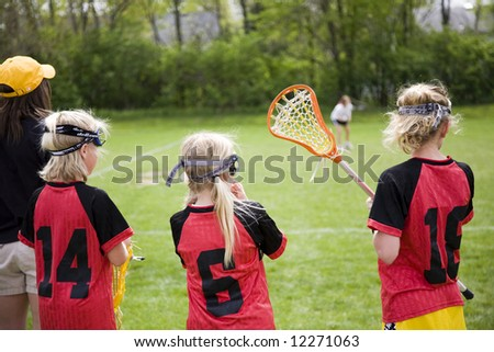 Female lacrosse players on the sideline of a game - stock photo
