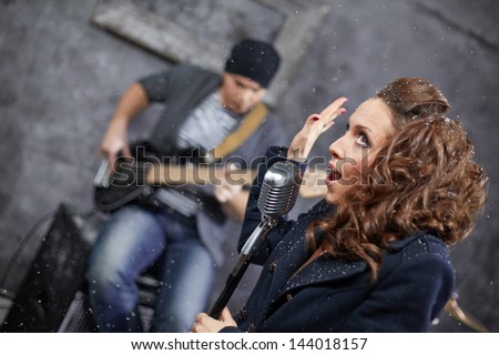 Female lead vocalist and guitarist in studio during shooting videp clip, turned frame - stock photo