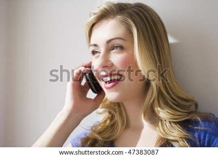 female leaning against wall and talking on cell phone - stock photo
