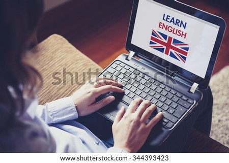 Female learning british english at home with a laptop computer at home. - stock photo