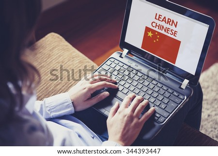 Female learning chinese at home with a laptop computer at home. - stock photo