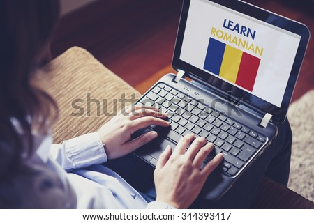 Female learning romanian at home with a laptop computer at home. - stock photo