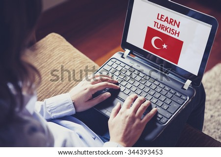 Female learning turkish at home with a laptop computer at home. - stock photo