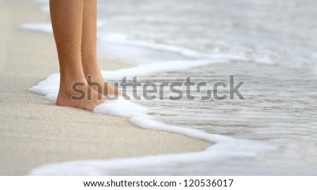 Female leg walking on the beach in the ocean - stock photo