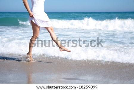 Female leg walking on the beach in the ocean - stock photo