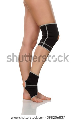 female leg with brace for knee and ankle - stock photo