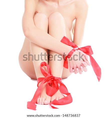 Female legs and hands with red ribbons on them - stock photo