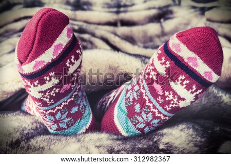 Female legs in Christmas socks under a blanket of fur. toning image - stock photo