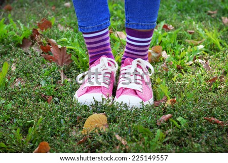 Female legs in colorful socks and sneakers outdoors - stock photo