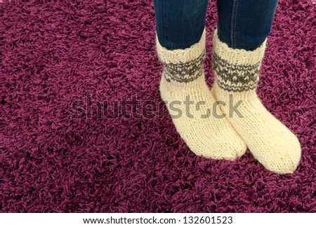 Female legs in colorful socks on color carpet background - stock photo