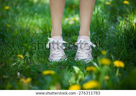 Female legs in pink shoes on the summer field - stock photo