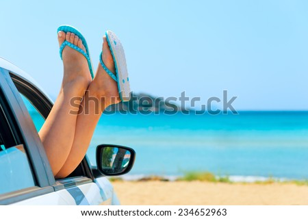 female legs in shales on sea background - stock photo