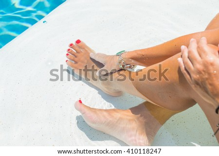 Female legs in the pool water selective focus and motion blur - stock photo