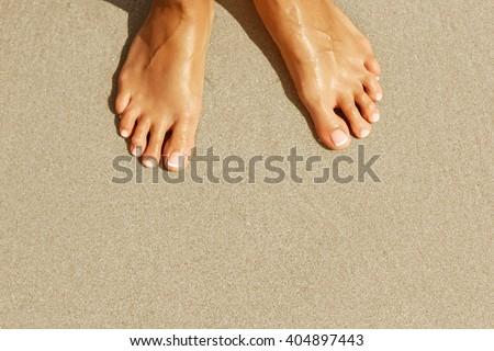 Female legs on beach. top view - stock photo