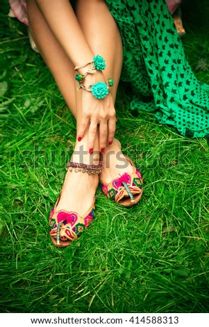 female legs on grass in leather ethnic boho summer sandals  - stock photo