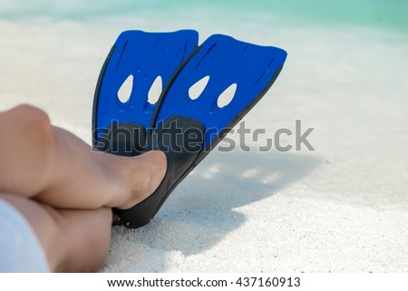 Female legs wearing fins, with beautiful white sand and turquoise sea in the background - stock photo
