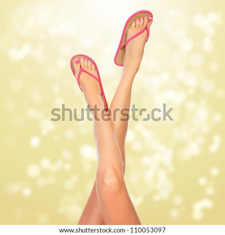 Female legs with pink flip-flops, blurred lights on background - stock photo