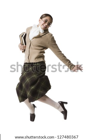 Female librarian with eyeglasses and books jumping and smiling - stock photo