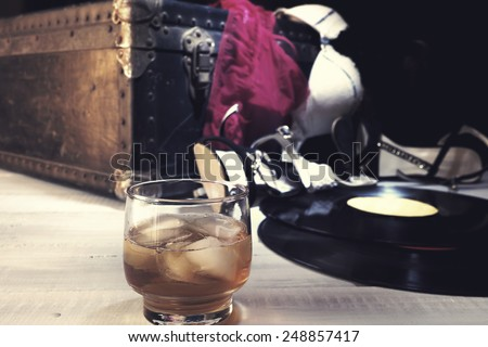 Female lingerie and accessories on vintage suitcase. Edited with faded colors and vintage effect. Shallow depth of field, focus on the glass of drink - stock photo