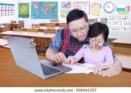 Female little student studying with male teacher in the classroom and using a book and laptop - stock photo