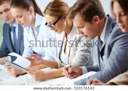 Female looking through business papers at briefing among her colleagues - stock photo