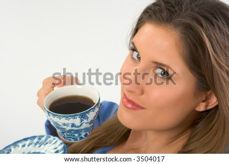 female looks up drinking her morning coffee - stock photo