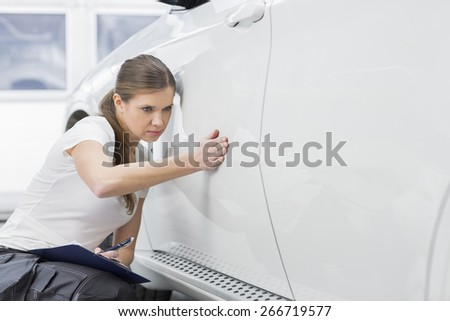 Female maintenance engineer examining car in workshop - stock photo