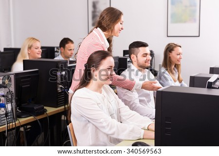 Female manager and employees working with computers at office. Selective focus on girl  - stock photo