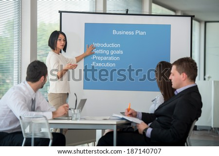 Female manager presenting data on whiteboard to coworkers - stock photo