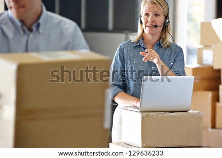 Female Manager Using Headset In Distribution Warehouse - stock photo