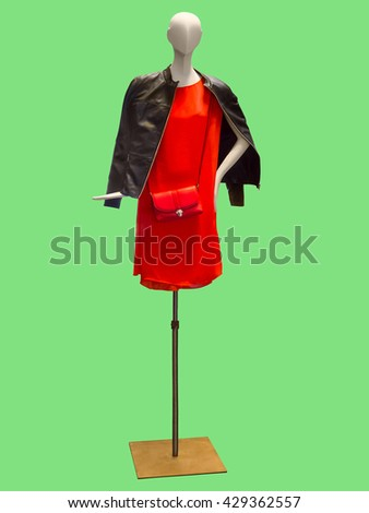 Female mannequin wearing red dress and leather jacket. Isolated on green background. No brand names or copyright objects. - stock photo