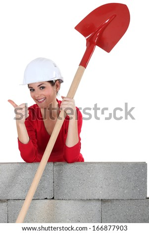 Female mason with shovel, giving the thumbs-up - stock photo