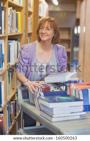 Female mature librarian returning books in library smiling at camera - stock photo