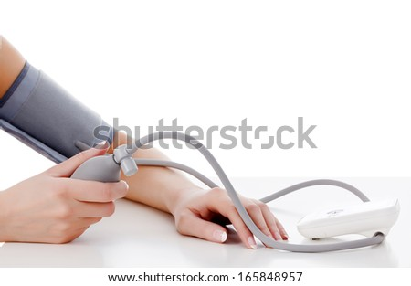 Female measures her blood pressure, white background, copyspace - stock photo