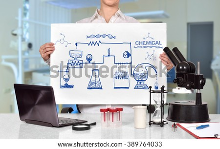 Female medical or scientific researcher holding poster with drawing scheme chemical reaction - stock photo