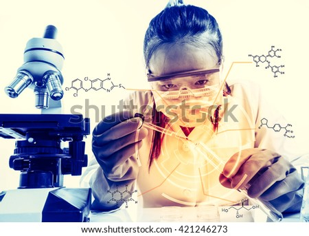 female medical or scientific researcher or woman doctor looking at a test tube of clear solution in a laboratory with her microscope beside her;with chemical equations. - stock photo