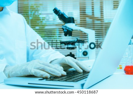 Female medical or scientific researcher or woman doctor using a computer in a laboratory with microscope and other equipment in the foreground,science people and selective focus. - stock photo