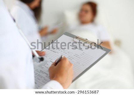 Female medicine doctor filling in patient medical history list during ward round. Medical care or insurance concept. Physician ready to examine patient and help - stock photo