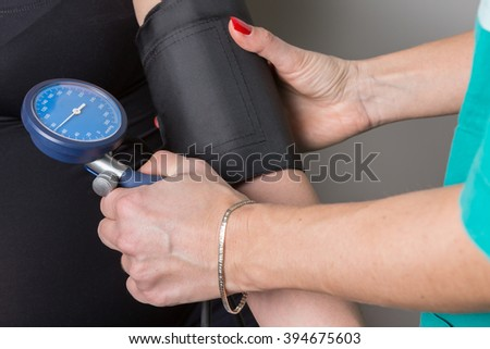 Female medicine doctor measuring blood pressure to patient. Medical concept. Hand of doctor and pregnant female patient while pressure measuring. - stock photo