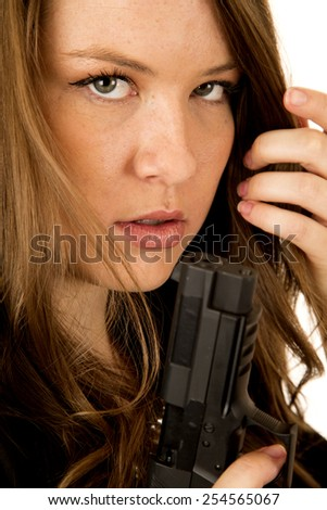 Female model holding pistol close up serious - stock photo