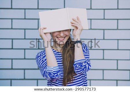 Female model with a white book on the background wall of the building - stock photo