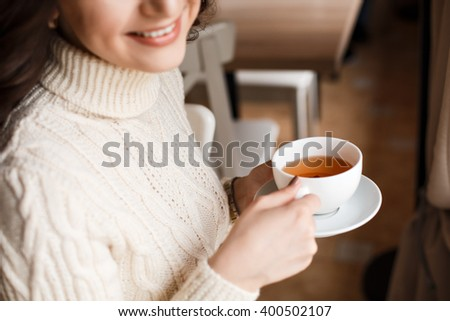 Female model with long hair. Amazing sensual girl with gorgeous make-up is enjoying a delicious coffee or tea, playfully smiling at the camera. Long dark wavy hair, white smile. - stock photo