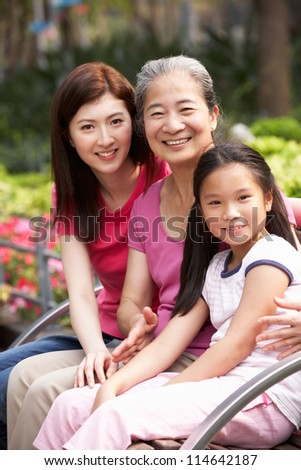 Female Multi Genenration Chinese Family Group Sitting On Bench In Park Together - stock photo