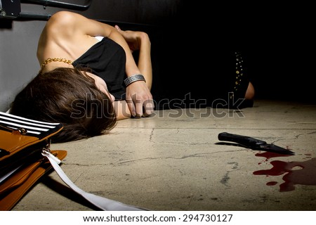 female murder victim laying on a dark alley with a bloody knife.  the crime scene is a dark street alley.  - stock photo
