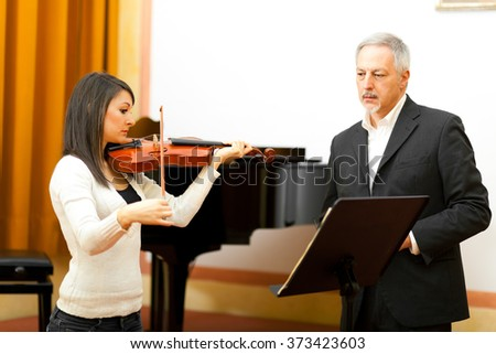 Female musician learning to play violin - stock photo