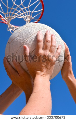 Female netball players struggle for a netball with a netball hoop and ring in the background. - stock photo